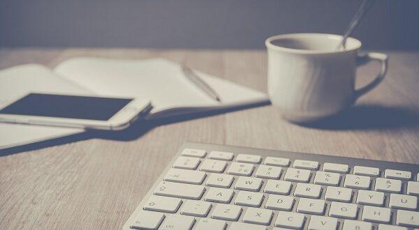 Klawiatura, notatnik, kubek z kawą i komórka.